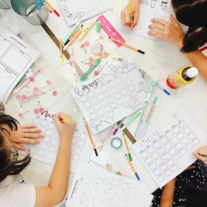 bullet journal workshop table with students lettering and drawing